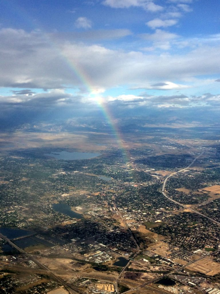 Rainbow as seen from an airplane leaving a city, capturing nicely how our amazing atmosphere is constantly a part of our lives.  Photo by Dr. Magi's sister.