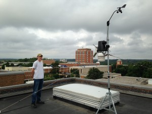 Warren Pettee with our Vantage Pro II weather station (courtesy of Dr Matt Eastin) that talks to our display on the 1st floor.  Atkins library, the tallest building on campus, is in the background.