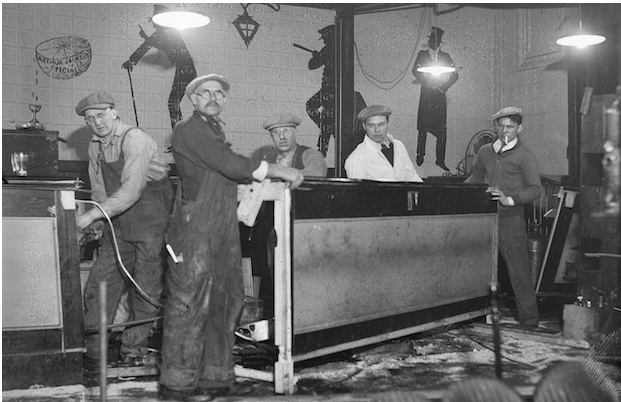 The agents pause yet again to pose for a photo amid the chaos of the ransacked speakeasy at 153 Causeway St. Prominently displayed in this photo are the caricatures painted on the wall of the hideaway. Two of the three figures are of high society men, both wearing top hats and one carrying a walking cane. The third figure wears a law officer's cap and carries a police baton, pointed at one of the other two figures, marking him as an agent of the law. He leans against one of the buildings support columns between the two other caricatures, an ironic reminder of the ever-present danger of being caught in such an establishment. The relaxed image of his leaning posture juxtaposed with his pointed baton denote the contrary legal status of alcohol sales at the time.