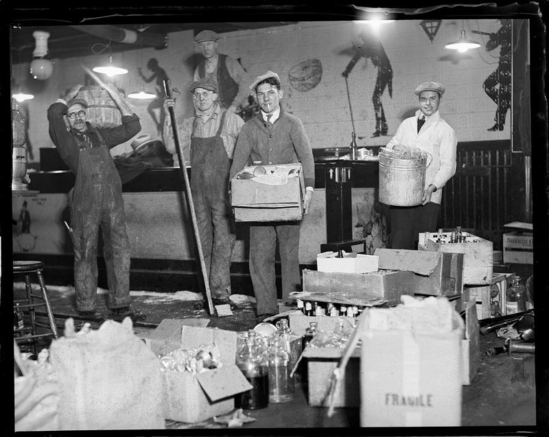 Five men pose for a picture inside a decorated speakeasy. Three of the men hold containers full of alcohol bottles like proud fishermen holding large prize bass, and boxes of alcohol rest among the trash being generated as the bar is disassembled.
